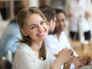 Business Coaching - lächelnde Frau am Arbeitsplatz
